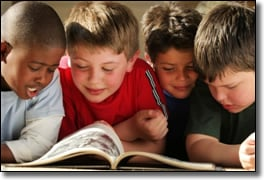 Four boys sharing a book