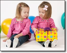 Cute little twin girls opening a polka-dot wrapped present